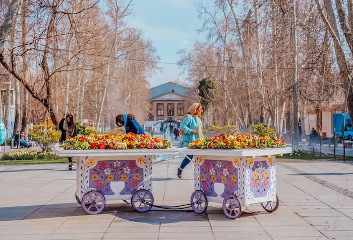 two girls behind bunch of flowers in Park Iran-min