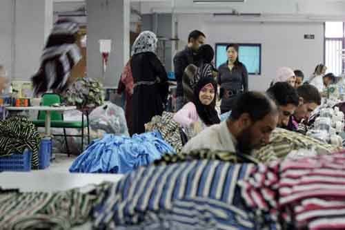 Chinese and Egyptian employees work together at the Chinese-owned Nile Textile Group factory in Port Said (AFP)