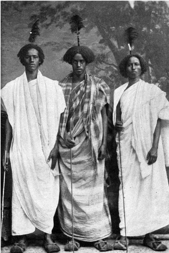 Colonial photograph of Somali men wear traditional white or plaid robes, brown shoes, and feather combs