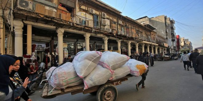 A man pulls a cart loaded with sacks near the Central Bank of Iraq's headquarters along Rashid Street in the center of Iraq's capital Baghdad, Dec. 22, 2020. (AFP Photo)